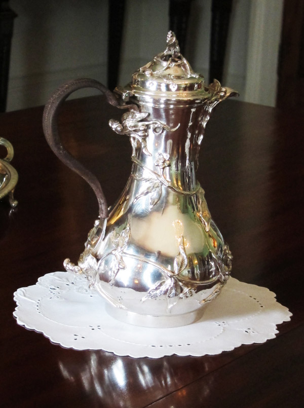 A fine hot-water jug from the 1750s, decorated with delicate floral tendrils in the manner of Paul De Lamerie, is part of a silver collection in a private house outside York.