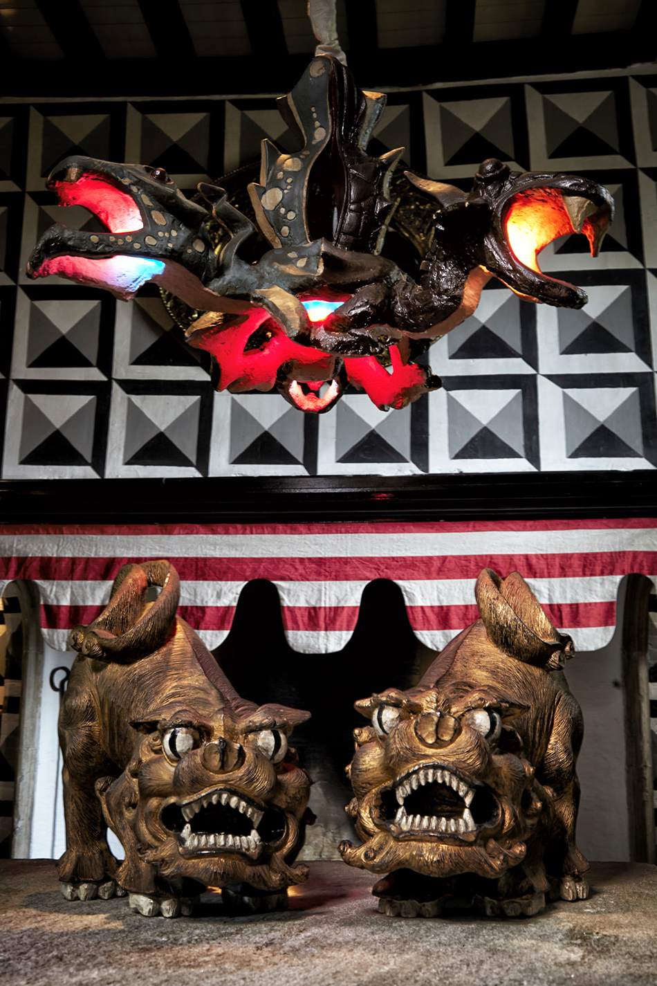 In the entrance hall, a pair of Chinese carved-wood dogs from the 1960s stand guard under a terra-cotta folk-art dragon chandelier from around 1950.