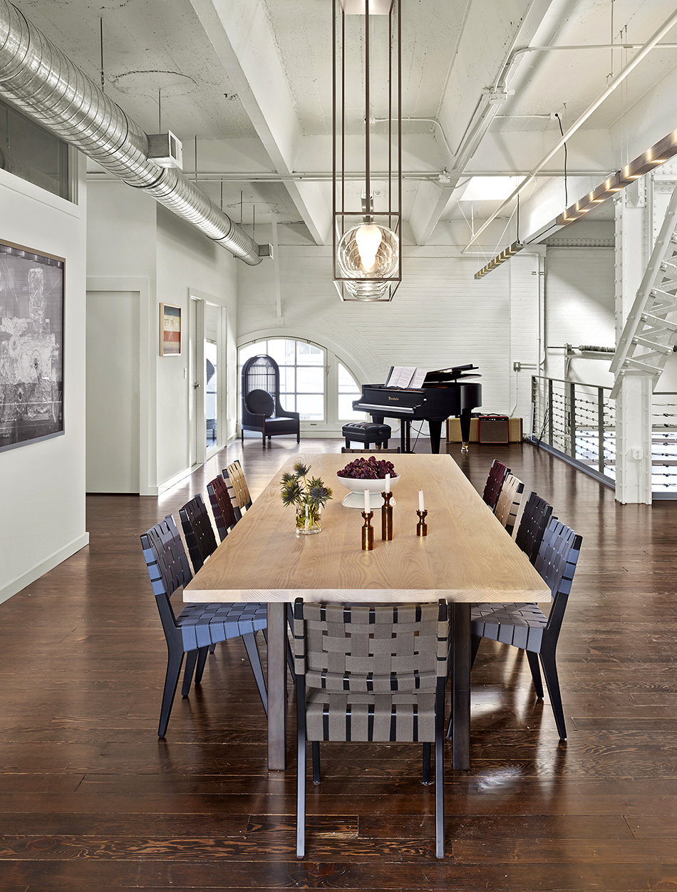 Geremia Design custom-made the light fixture and table in this combined gallery-living space, converted from a firehouse, in San Francisco's SoMa district. The dining chairs are vintage Jens Risom. Photo by Cesar Rubio