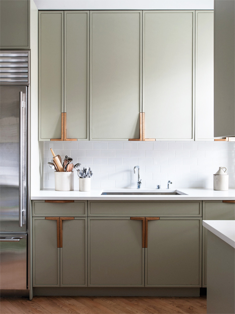 In this Park Slope kitchen, the plumbing fixtures are by Vola, and the cabinet faces are painted in Farrow & Ball's French Gray; the firm designed the handles to pick up the color of the wood floors.