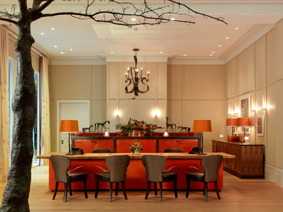 Red and copper hues bring warmth to the reception area of Coworth Park, a hotel outside London.