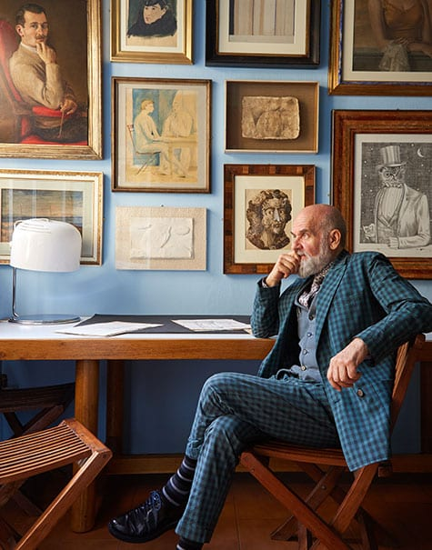 Barnaba Fornasetti sits before a collection of paintings by his father.