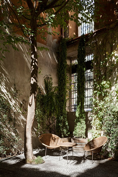 A set of vintage rattan furniture is arranged in Six Gallery's outdoor garden space. Photo by Alberto Strada