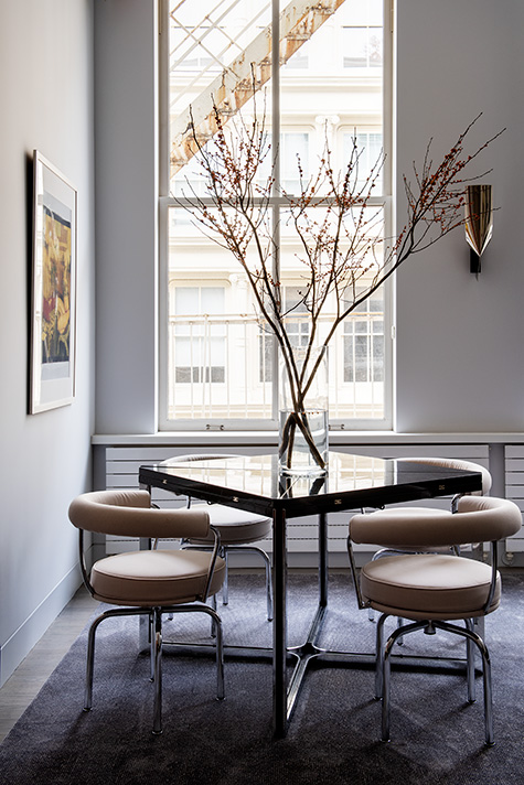 flip-top lacquer-and-steel dining table is surrounded by a set of Charlotte Perriand LC7 chairs by Cassina